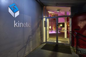 Photo of Kinetic's front door and exterior logo at night.
